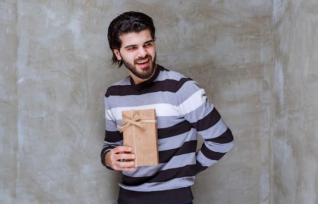 Mężczyzna w pasiastej koszuli, trzymający kartonowe pudełko i uśmiechający się