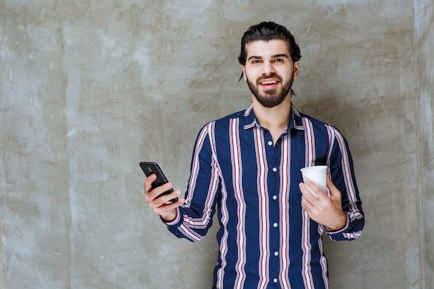 Mężczyzna w pasiastej koszuli trzymający kubek z wodą i bawiący się telefonem