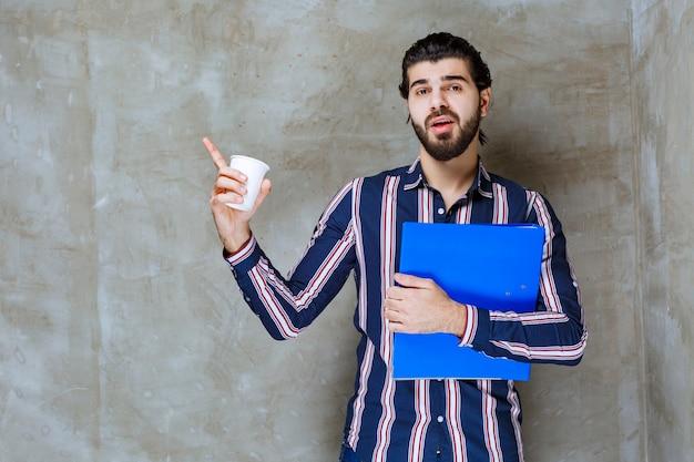 Mężczyzna w pasiastej koszuli, trzymający niebieską teczkę i białą, jednorazową filiżankę
