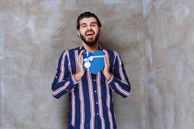 Mężczyzna w pasiastej koszuli trzymający niebieskie pudełko w kształcie serca