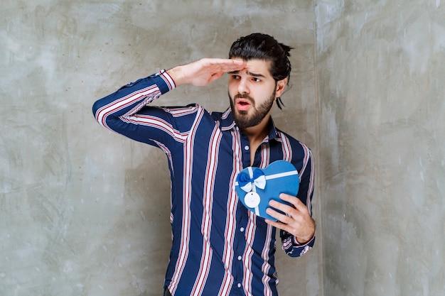 Mężczyzna w pasiastej koszuli, trzymający pudełko w kształcie niebieskiego serca i czekający na nominację