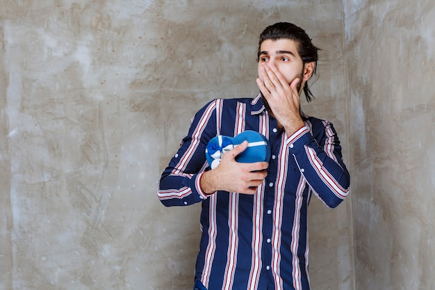 Mężczyzna w pasiastej koszuli, trzymający pudełko w kształcie niebieskiego serca i wygląda na zachwyconego i przestraszonego