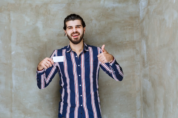Mężczyzna w pasiastej koszuli trzymający swoją wizytówkę i cieszący się nową pozycją