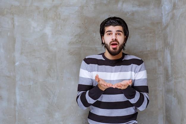 Mężczyzna w pasiastej koszuli wygląda na zaskoczonego i zdezorientowanego