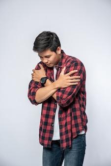 Mężczyzna w pasiastych koszulach stał chory i założył ręce.