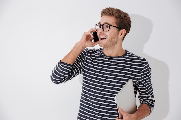 Mężczyzna w pasiastym swetrze rozmawia przez telefon i trzyma laptopa w jednej ręce. na białym tle szarym tle
