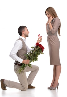 Mężczyzna w pełnym garniturze stojący na jednym kolanie i składający propozycję.