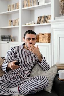 Mężczyzna w piżamie ogląda telewizję i trzyma pilota
