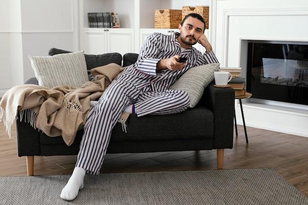 Mężczyzna w piżamie przed telewizorem
