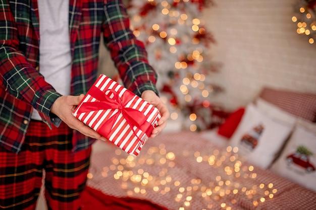 Mężczyzna w piżamie trzymający prezent gwiazdkowy