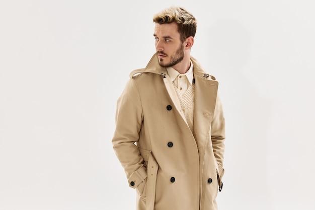 Mężczyzna w płaszczu trzyma ręce w kieszeniach modny styl nowoczesny wygląd z boku na jasnym tle