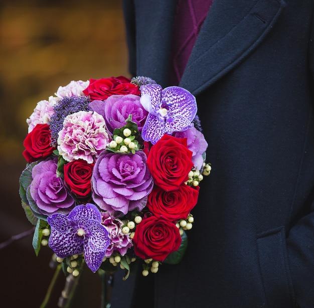 Mężczyzna w płaszczu z bukietem czerwonych i fioletowych kwiatów mieszanych.