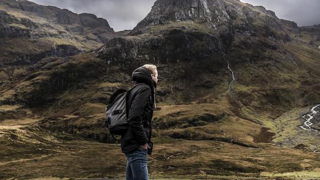 Mężczyzna w plecaku i ciepły płaszcz idący po górach szkocji pod szarym niebem