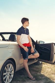 Mężczyzna w pobliżu samochodu kabriolet na zewnątrz