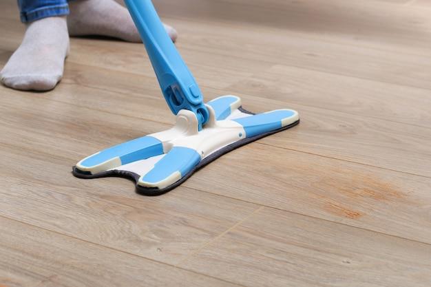 Mężczyzna w pokoju myje podłogi mopem. pod łóżkiem. czyszczenie.
