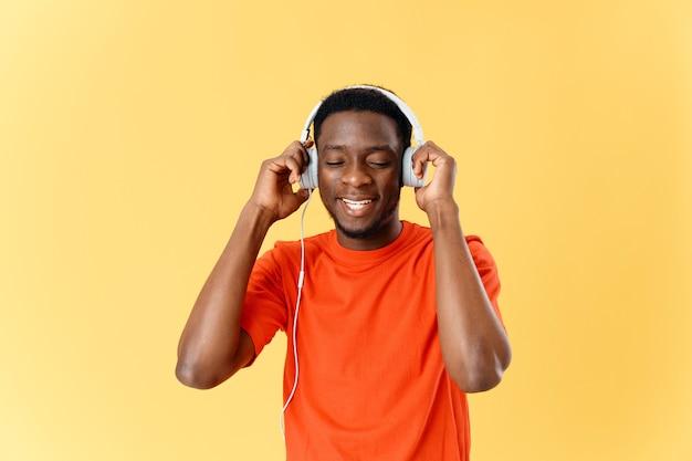 Mężczyzna w pomarańczowej koszulce ze słuchawkami do słuchania muzyki