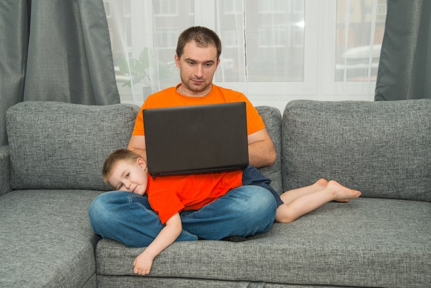 Mężczyzna w pomarańczowej koszuli próbuje pracować na laptopie, podczas gdy syn mu przeszkadza. praca w biurze domowym i poczęcie w domu