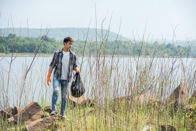 Mężczyzna w pomarańczowych rękawiczkach zbierających śmieci w czarnej torbie.
