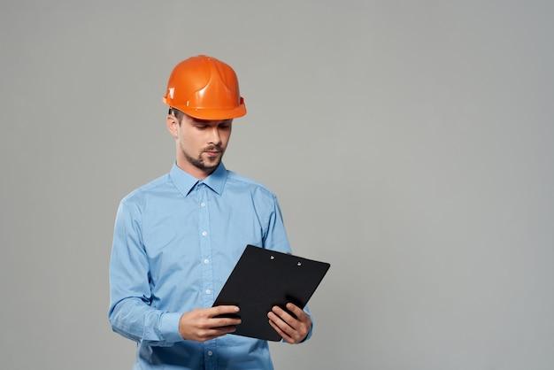 Mężczyzna w pomarańczowym hełmie plany budowniczego na białym tle