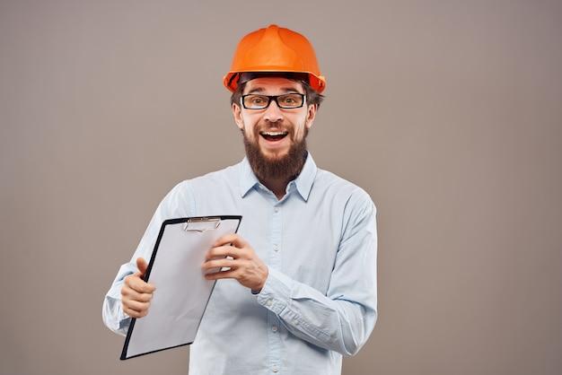 Mężczyzna w pomarańczowym kasku inżynier planuje prace budowlane