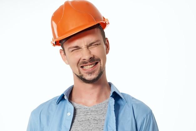 Mężczyzna w pomarańczowym kasku ochrony zawodu roboczego