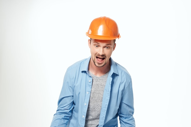 Mężczyzna w pomarańczowym kasku profesjonalnej pracy na białym tle