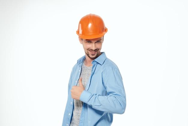 Mężczyzna w pomarańczowym twardym kapeluszu konstrukcja bezpieczeństwa pracy jasnym tle