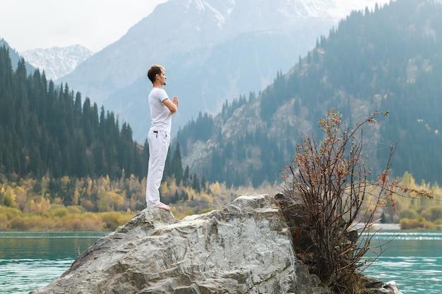 Mężczyzna w pozie samasthiti na kamieniu wśród górskiego jeziora.