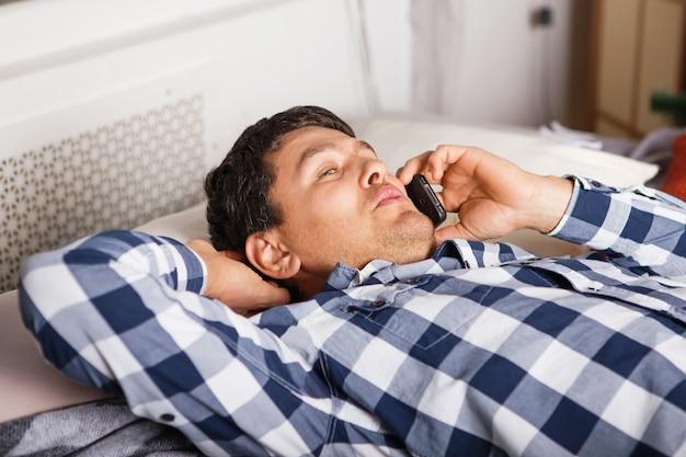 Mężczyzna w pozycji leżącej rozmawia przez telefon komórkowy w domu