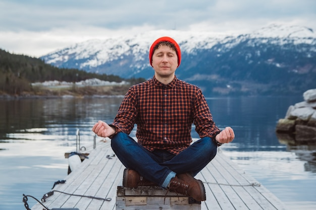 Mężczyzna w pozycji medytacyjnej siedzący na drewnianym molo na tle góry i jeziora