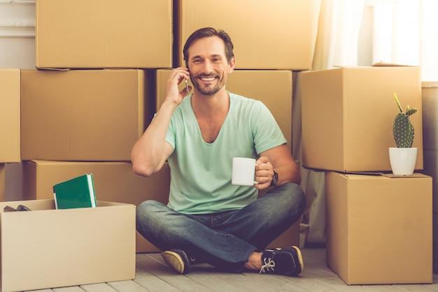 Mężczyzna w przypadkowych ubraniach siedzi na podłodze wśród pudeł