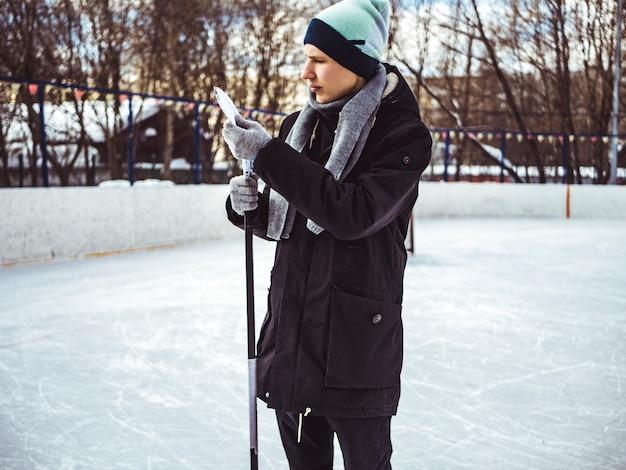 Mężczyzna w przypadkowych ubraniach stojący na zewnątrz na hokcey lodowisku z kijem