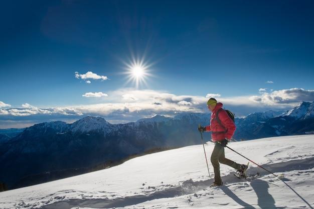 Mężczyzna w rakietach śnieżnych i kijkach trekkingowych