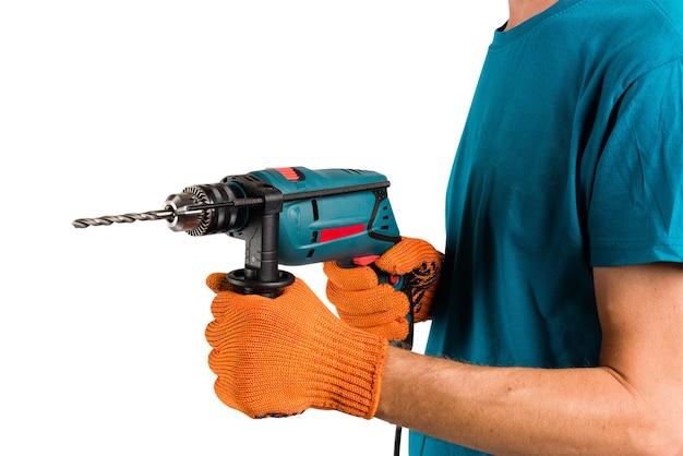 Mężczyzna w rękawicach ochronnych zmienia wiertło w perforatorze elektrycznym przy wycięciu