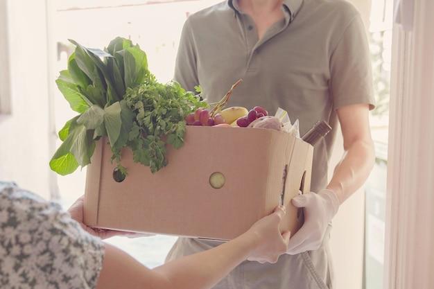 Mężczyzna w rękawiczkach dostarcza do domu pudełko z jedzeniem, wolontariusz trzymający pudełko z zakupami na datek społeczności