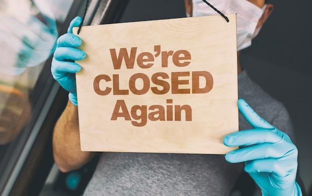 Mężczyzna w rękawiczkach i masce medycznej trzyma ten drewniany znak z napisem: znowu jesteśmy przy wejściu do kawiarni