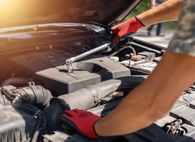 Mężczyzna w rękawiczkach naprawiający i naprawiający samochód z kluczem i otwartym kapturem!