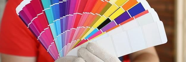 Mężczyzna w rękawiczkach pokazuje próbki kolorów w krzywym zarysie paletę kolorów do tworzenia