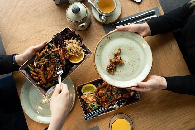 Mężczyzna w restauracji opiekuje się kobietą i kładzie jedzenie na jej talerzu.