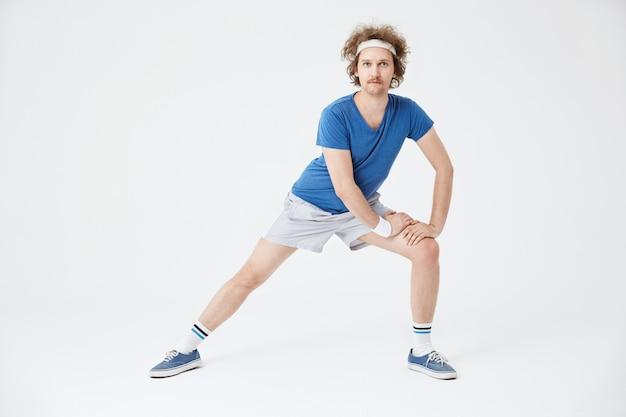 Mężczyzna w retro odzież sportowa rozgrzewa mięśnie przed treningiem