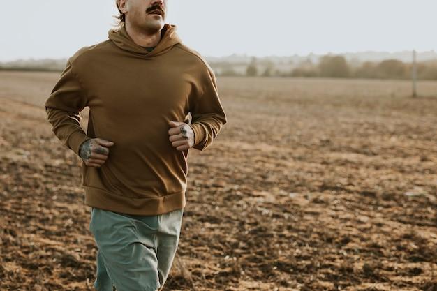 Mężczyzna w rozciągliwej bluzie z kapturem na wsi o zachodzie słońca