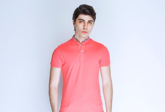 Mężczyzna w różowej koszuli daje neutralne pozy.