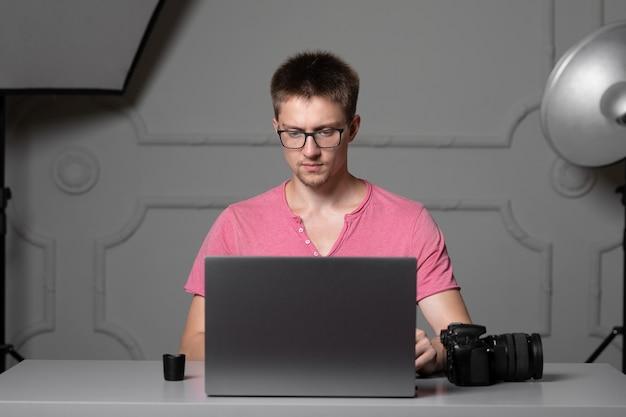 Mężczyzna w różowej koszuli i okularach pracujący na laptopie