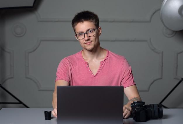 Mężczyzna w różowej koszuli i okularach siedzi przy stole we wnętrzu studia i pracuje na laptopie
