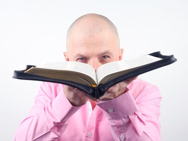 Mężczyzna w różowej koszuli z otwartą biblią w rękach