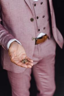 Mężczyzna w różowym garniturze trzyma dwie obrączki