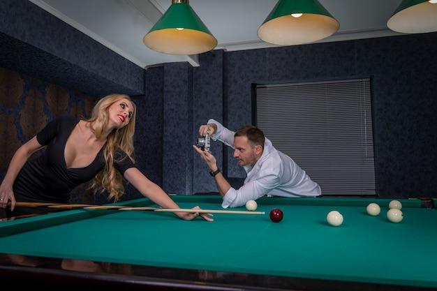 Mężczyzna w sali bilardowej fotografujący młodą seksowną kobietę