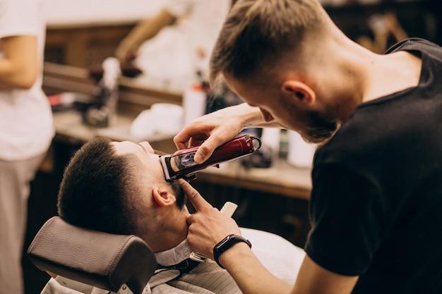 Mężczyzna w salonie fryzjerskim robi fryzurę i przycinanie brody