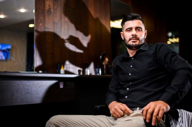 Mężczyzna w salonie fryzjerskim z widokiem na kamerę