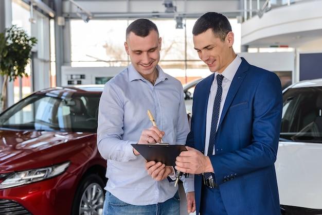 Mężczyzna w salonie podpisuje umowę kupna samochodu